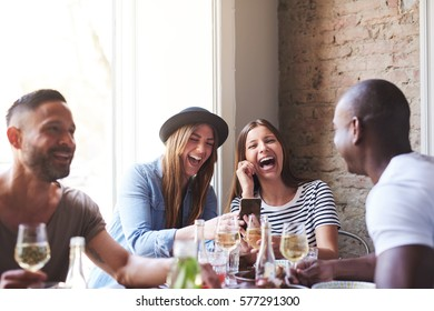 Small group of four diverse friends laughing at something on phone at dinner table in restaurant
