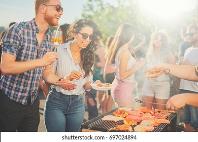 Small group of friends drinking alcohol and having a meal at barbecue party