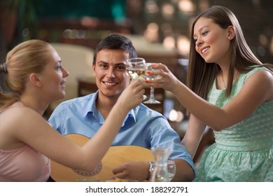 Small group of friends enjoying dinner and music together in a restaurant.