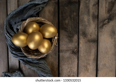 Small group of the golden easter eggs in birds nest over rustic wooden background top view with copy space, horizontal orientation