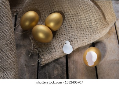 Small group of the golden eggs in birds nest over rustic wooden background and two empty broken golden eggs. Success Symbol or Happy Easter Concept.