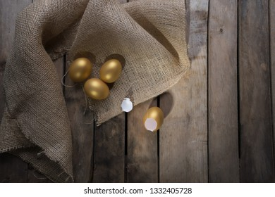 Small group of the golden eggs in birds nest over rustic wooden background and two empty broken golden eggs. Success Symbol or Happy Easter Concept. Top view with copy space