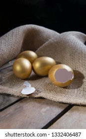 Small group of the golden eggs in birds nest over rustic wooden background and two empty broken golden eggs. Success Symbol or Happy Easter Concept. Vertical orientation