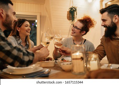 Small group of happy friends having fun while toasting during dinner at home. Focus is on redhead woman.