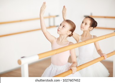 Small group of little girls in ballet dresses looking at their raised hands while training in classroom