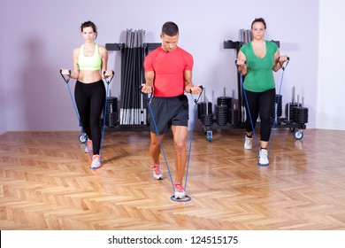 Small group of people doing bicep exercise using resistance bands