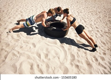 Small group of people doing push-ups on tire. Young athletes working out on beach during a hot summer day.
