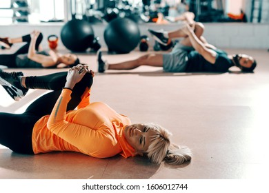 Small group of people with healthy habits doing stretching exercises on a gym floor. Selective focus on blonde woman. In background mirror.
