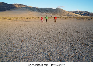 A small group of people stand on the desert playa in front of sand dunes.