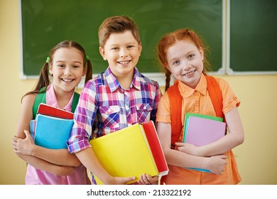 Small group of school friends looking at camera on background of blackboard