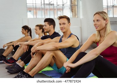 Small group sits side by side on floor of gym while waiting to exercise