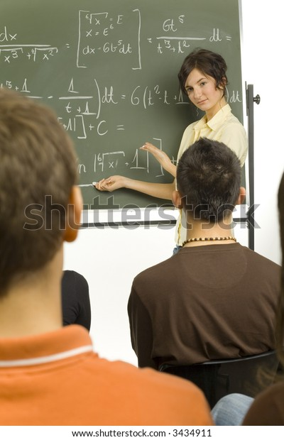 Small group of teenagers sitting in front of blackboard. One girl standing  beside the blackboard and showing something to the rest