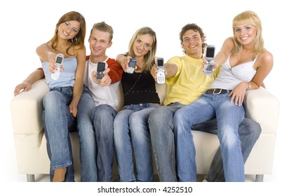 Small group of teenagers sitting on couch. Smiling and showing mobile phones. Looking at camera. White background, front view