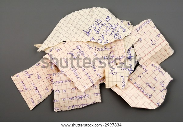Small group of torn notebook paper isolated over grey