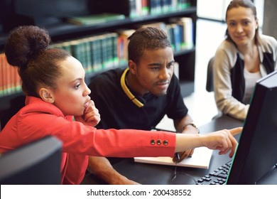 Small group of university students working on computer in a library. Young people finding information for their college assignment.