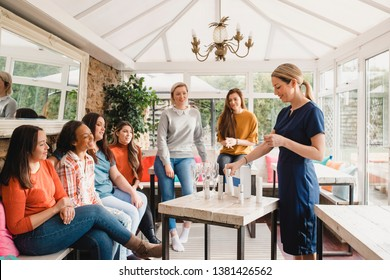 Small group of women with a mixed age range sitting together at a beauty product party. The beauty product sales representative is standing talking about the products.