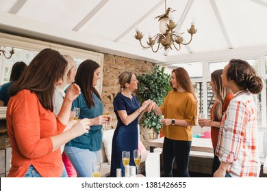 Small group of women with a mixed age range at a beauty product party. The beauty product sales representative is standing talking about the products.