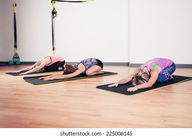 A small group of women are practicing yoga in a gym