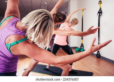 A small group of women are stretching in the gym