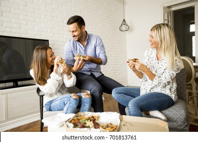 Small group of young friends eating pizza in the room