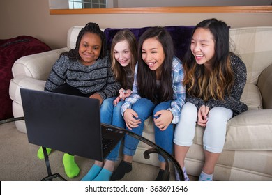Small group of young girl friends watching streaming tv on compu