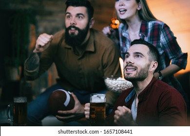 Small group of young people cheering for their rugby team while watching spots match on TV at home.