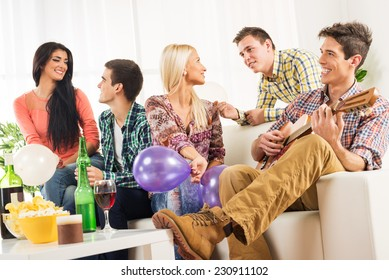 A small group of young people hang out at the house party, chatting with each other while their friend having fun playing acoustic guitar.