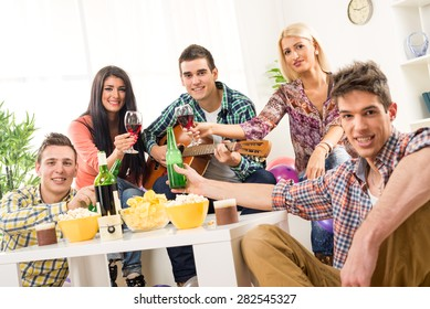 Small group of young people at the home party, enjoy the sounds of the acoustic guitar, drinking wine and beer. Looking at camera.