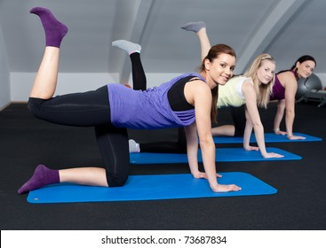 A small group of young women doing butt exercises
