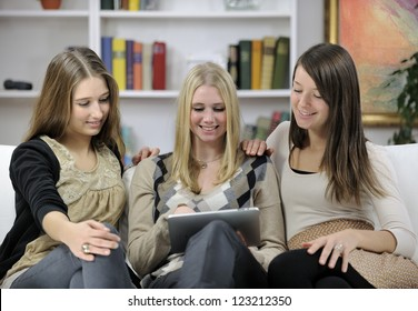 Small group of young women using digital tablet at home