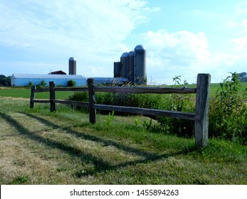 Small guard fence with a group of silos and barn in the background with clouded blue sky.