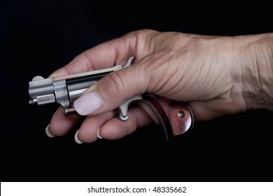 Small gun concealed in lady's hand. Focus on gun.