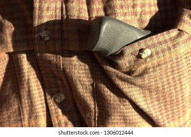 Small gun in the shirt's pocket.