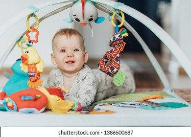 A small, half-year-old boy is playing on the floor in the room with his toys