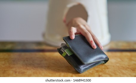 A small hand stealing a wallet.