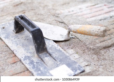 Small hand tools, a float trowel and a masonry trowel, left at the construction site