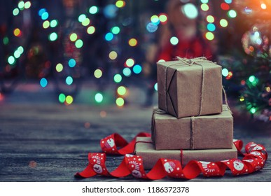 Small handmade gift boxes in shiny colorful night.  Luxury New Year gift. Christmas gift. Christmas background with gift box. Christmas time celebration. With copy space.