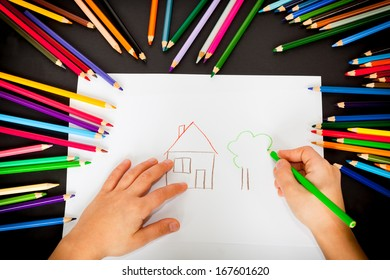 Small hands and colorful crayons at the black background