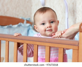 Small happy baby holding mother hand standing in bed with love