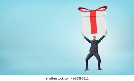 A small happy businessman standing on blue background and holding a giant gift box with both hands. Unexpected fortune. Lottery winner. Promotion and bonuses.