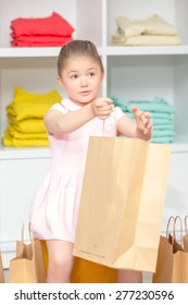 Small happy girl stretching her hands with the packages with a new dress in a fashion store