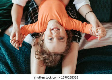 Small happy little girl laughing and looking straight on camera. Young woman holding her hands. Sitting on bedroom. Positive emotion. Upside down