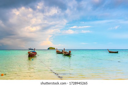 Small harbor with long tail boats at Ko Lipe island, Thailand, shortly before tropical storm. Big and heavy dark clouds above sea. Detail of wooden boats typical for Thailand.