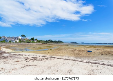 The small harbour at Kermengi, Brittany, at low tide. A small rowing boat rests on the sand.