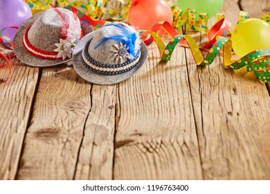 Small hats with feathers stuck in them and round multicolored balloons sitting on rustic wooden table