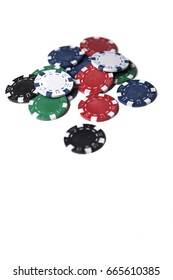 A small heap of different coloured gaming chips isolated on a white background