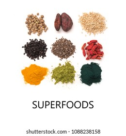 Small heap of various superfoods isolated on white background. Superfood as chia, spirulina, matcha tea powder, raw cocoa bean, goji, hemp, quinoa, black sesame, turmeric. Copy space for text.Top view