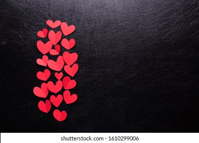 A lot of small hearts of red color against a black isolated background. Happy Valentine's Day.