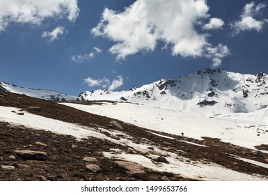 Small hiker at snow mountain valley against cloudy sky in Kazakhstan