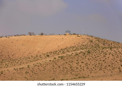Small hill in desert with Chanukiah under blue sky